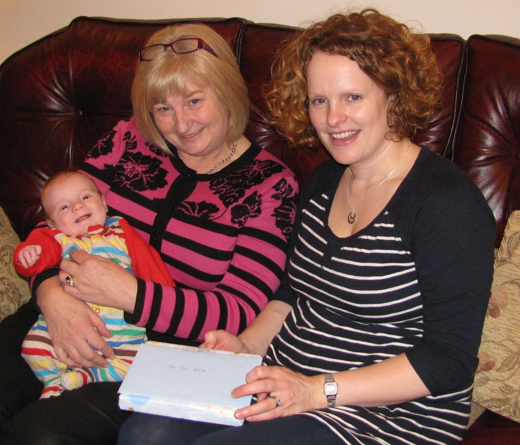 Caelan Meikle son of Beverley Meikle receives a Bible from Hilda Carlisle on behalf of the Touch Team Baby Bible Ministry.
